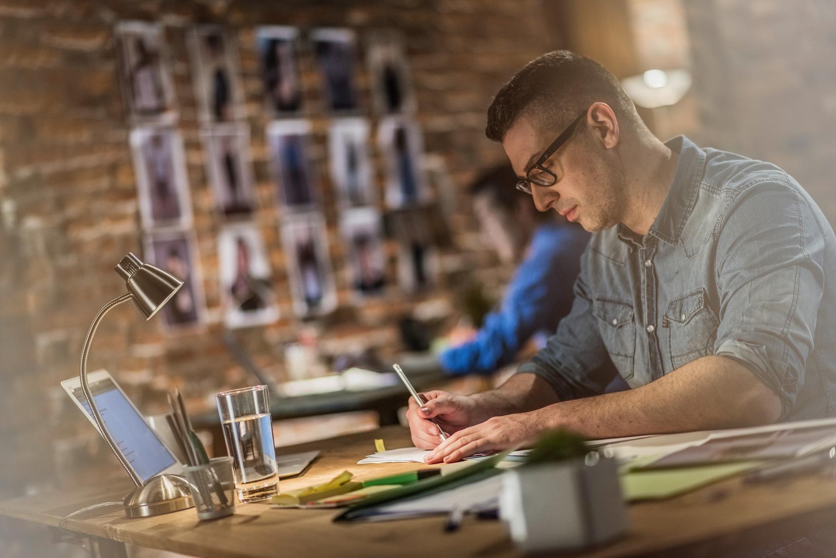 Graphic designer making sketches behind a desk