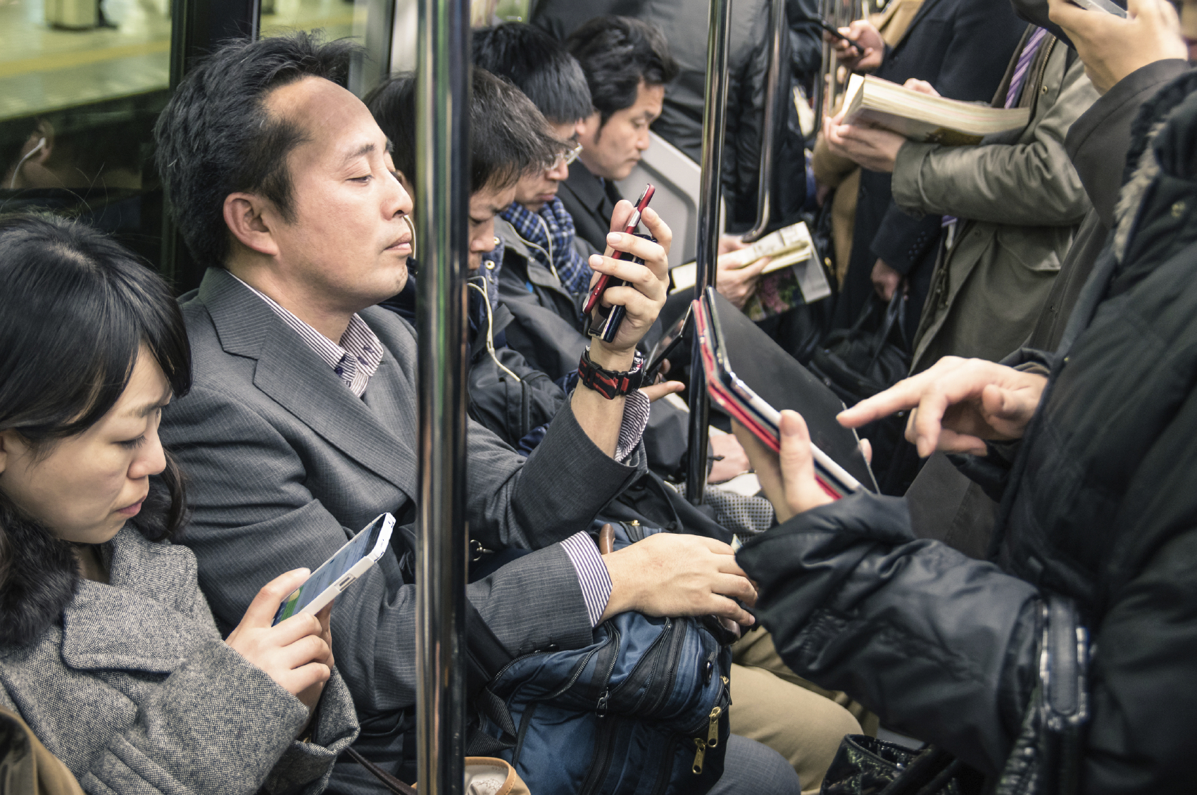 TOKYO -MARCH 2, 2015: people busy with smartphones and tablets i