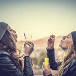 Friends with knitted cap having fun and blowing bubbles outdoors
