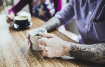 A trendy hipster man and woman with tattoos smile and talk as they enjoy a coffee and latte at a bright cafe, sitting at a large bamboo wood table.  Vertical overhead shot with copy space.